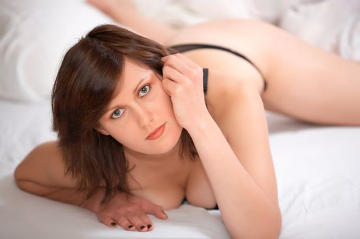 Young beautiful woman lies on bed