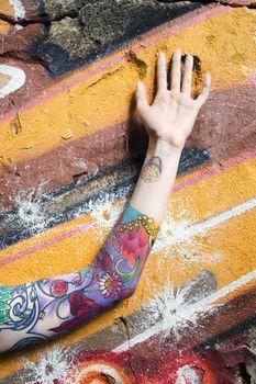 Tattooed Caucasian woman's arm against graffiti covered wall.