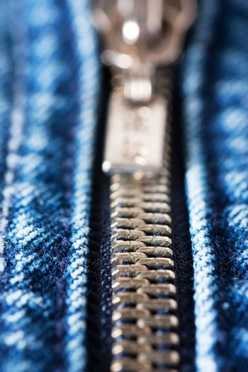 Macro shot of closed zipper on a blue jeans. Shallow depth of field