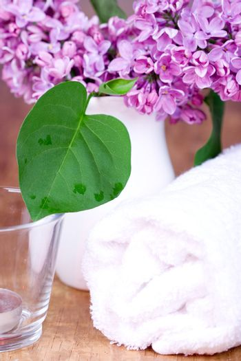 rolled towel, lilac and candle