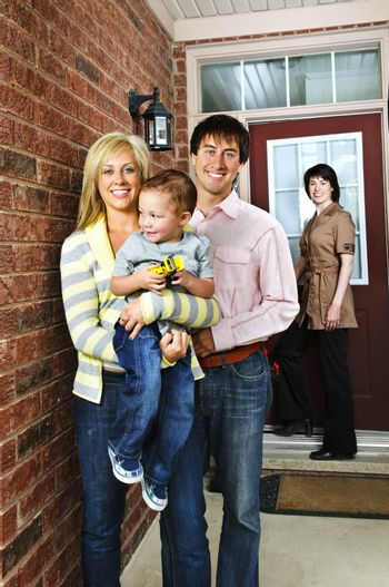Real estate agent with family welcoming to new home