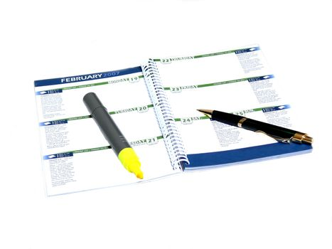 A calendar note pat with a pen and an marker over white.