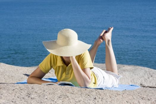 Womand reading a book while lying on a rock at the sea