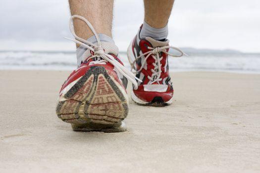 Feet of man jogging on a beach