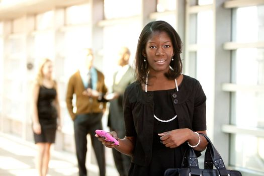A business woman with a smart phone with colleagues in the background