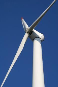 Close-up of wind turbine against blue sky