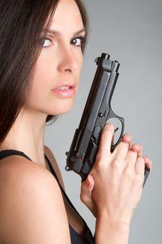 Sexy brunette woman holding gun