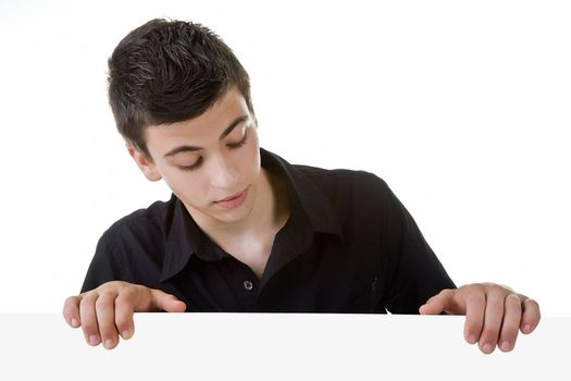 Young man, looking down to a blank board, with curious expression.