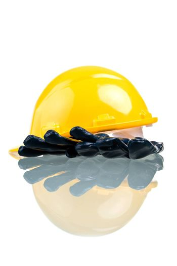 Construction hat and gloves, isolated on white background with reflection.