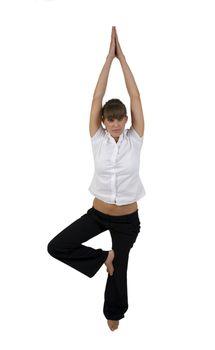 woman practicing yoga on one leg in studio