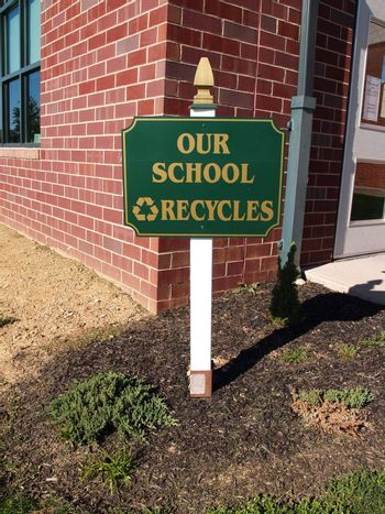recycling sign by a school buildin