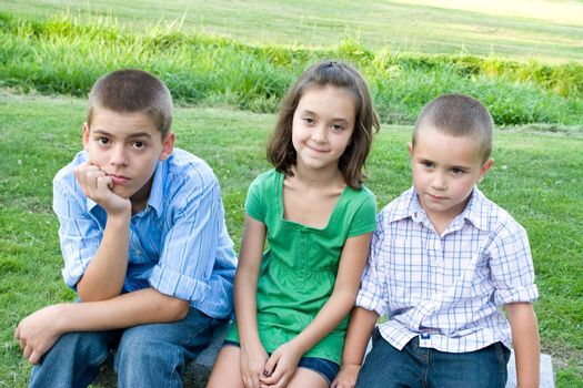 Three kids looking bored and overtired seated on a bench outdoors.