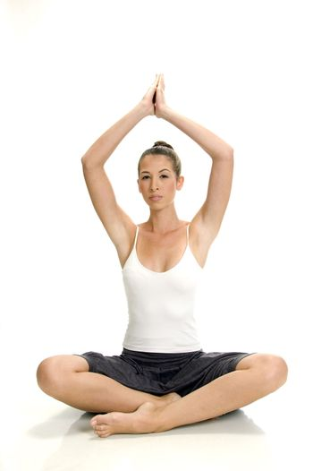 young woman doing yoga on an isolated white background