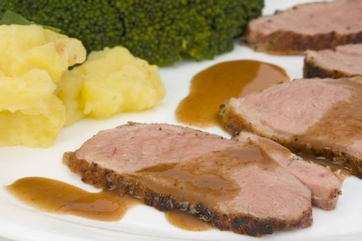 slices of a roasted duck fillet on a white plate