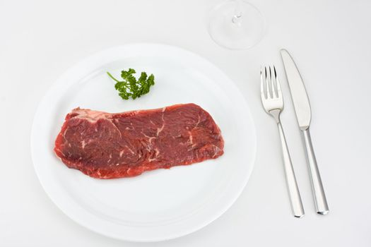 raw steak on a white plate with cutlery