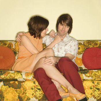 Pretty Caucasian mid-adult woman flirting with shy Caucasian mid-adult man sitting on colorful retro sofa.