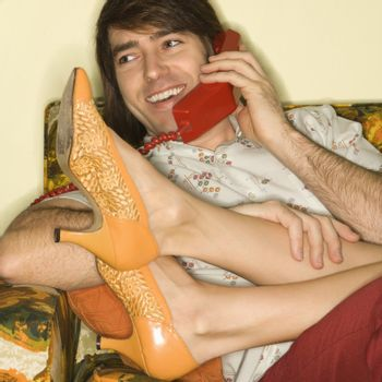Caucasian mid-adult man talking on telephone with Caucasion mid-adult woman's legs draped over lap.