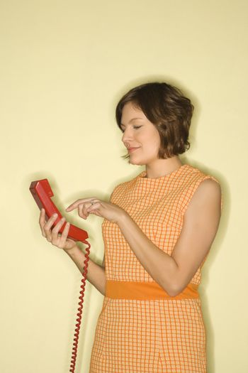 Woman dialing telephone.