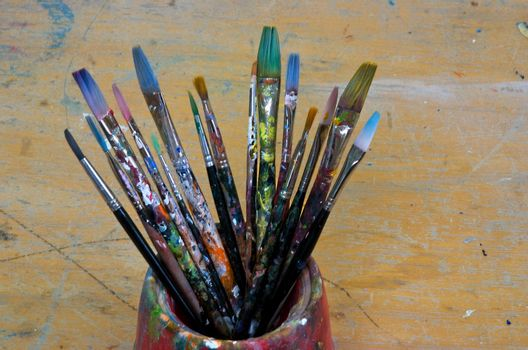 Several artist brushes in a pot, all have been used many times