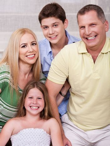 Portrait of happy familyof four posing and looking at you