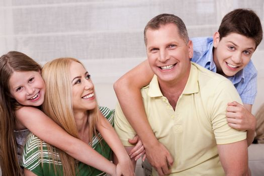 Portrait of lovely family having fun together in living room and looking at you
