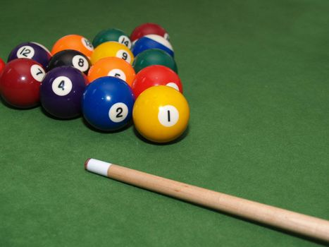pool balls and stick racked and ready on a billiards table