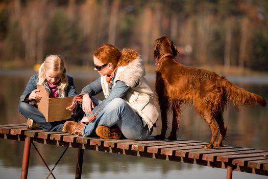 A girl reading a book with her mom at the lake in the forest, is a warm, sunny autumn day.
