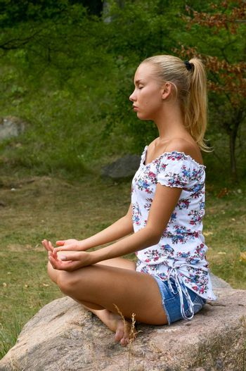 pretty blonde girl meditating on the stone in nature scenic
