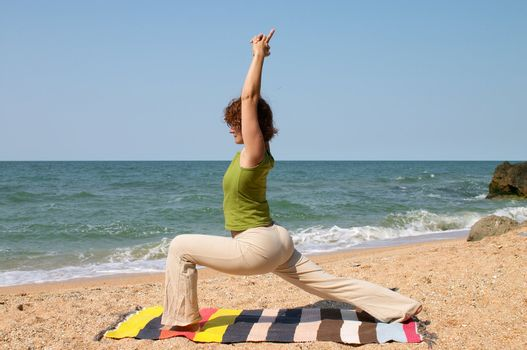 woman practice yoga asana virabhadrasana at seaside