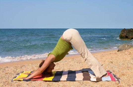 girl doing Adho Mukha Svanasana yoga pose on sea beach