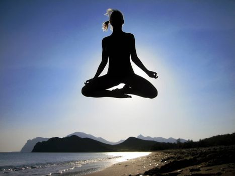 Female yogi flying over the beach