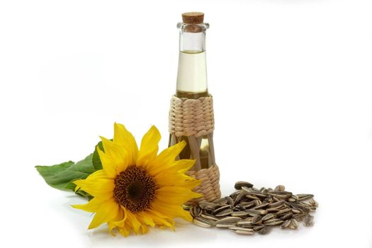 Salad oil in a glass bottle with sunflower and sunflower seeds on white background