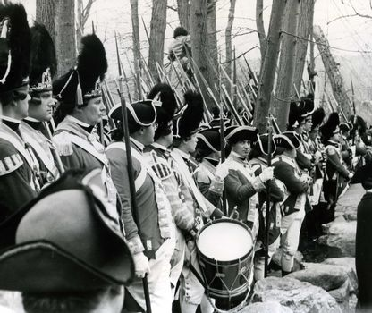 Photo was taken near the North Bridge in Concord, MA on April 19, 1975. These people were dressed in old Patriot military uniform and were part of a crowd estimated at 110,000 gathered to view a parade and celebrate the Bicentennial. President Gerald Ford delivered a major speech near the Concord North Bridge to this crowd.