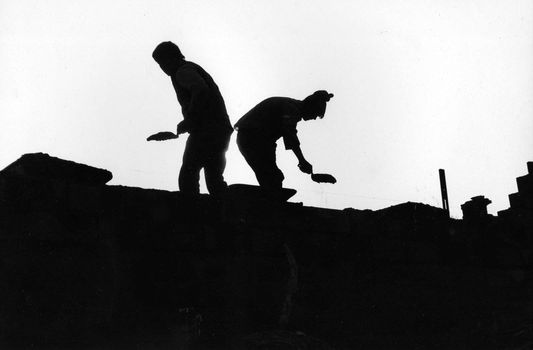 two masons silhouetted as they work on the roof of a building