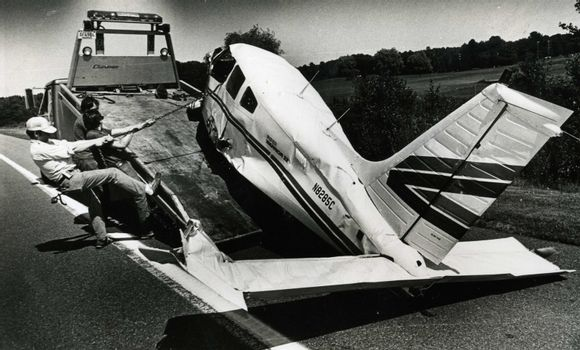Tow truck driver pulls damaged plane on to the flat bed tow truck.