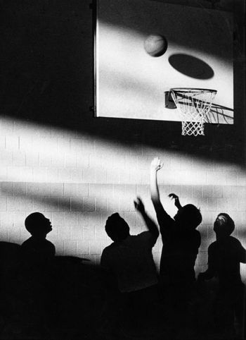 Young men playing basketball with a silhuette creating an artistic look.