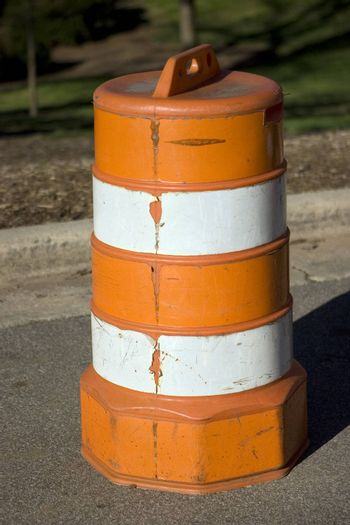 The side of a traffic barrel on the road next to a curb.
