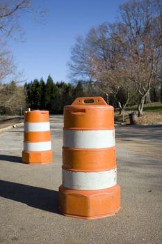 Two traffic barrels blocking off part of a road.