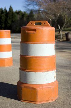 An orange traffic barrel on a small road.