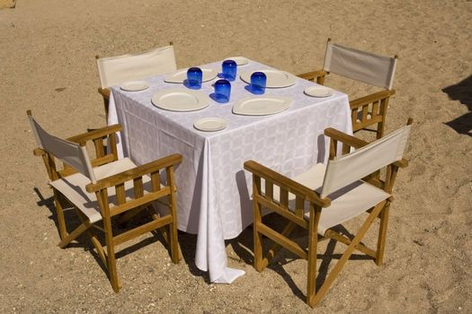 Table dressed for four on the beach, with white plates and blue glasses