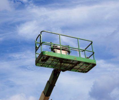 A green mechanical iift on top of a cloudy blue sky
