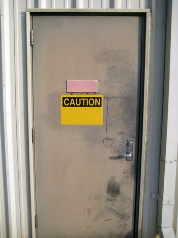 A worn metal door with a blank caution sign on it.