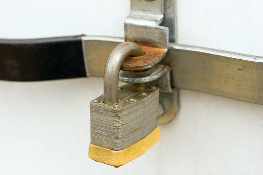 A padlock locking a door handle.