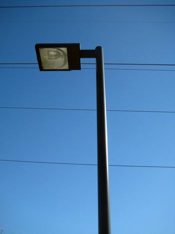 A tall black lamp post and some power lines on a clear blue sky.