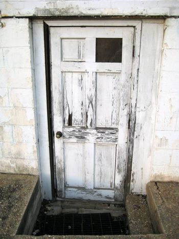 An old white beaten up doorway with paint chipping off.