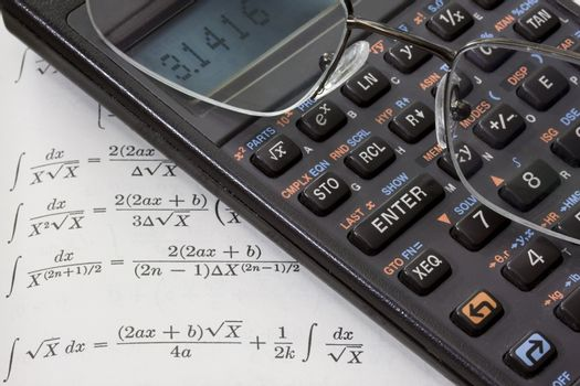 Scientific calculator with pi number on a display and reading glasses against math text book with integral tables. These are real devices, not props, showing some wear and dust.
