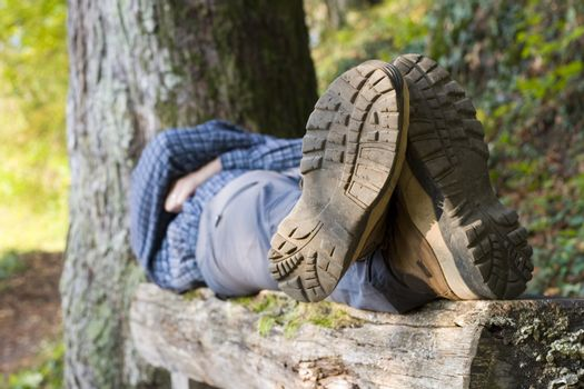 Hiker lying on a wooden bench. Focus on the boots in the foreground.