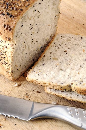 sliced of fresh seeded bread on a wooden board with bread knife