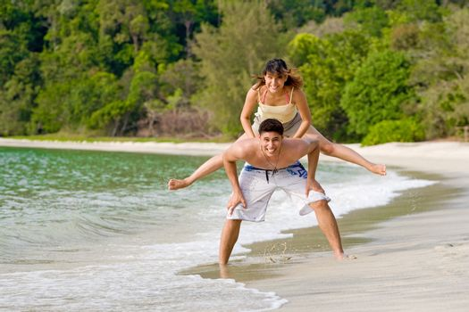 a couple playing leapfrog at the beach