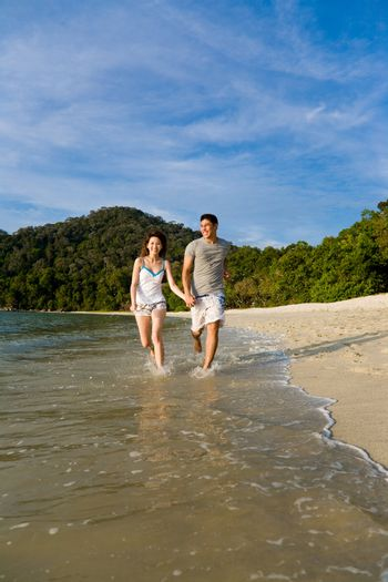 loving young couple running on the beautiful tropical beach